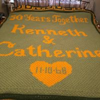 """My latest creation was indeed a labor of love. I began designing this King-sized 50th Anniversary Afghan (aka C2C graphghan) in February 2018. I used @stitchfiddle to graph my design. The C2C portion (middle) consisted of 236 rows. There are 42 granny squares around the perimeter and many varying stitches within. I used green and gold because they were my parents' wedding colors. I was finally able to present to my parents on their 50th Anniversary, November 10, 2018. Seeing their smiling faces was worth all of the love, determination, and hours that I put into it. I worked on it 7 out of 9 months with most of the work being done in the last 4 months. Unfortunately, I didn't keep track of my hours, but many evenings were spent """"hooking"""" while watching/listening to YouTube, Netflix, and Audible. The photos show just some of the progress from July onward. #crochet #crochetlove #crochetloversofinstagram #c2ccrochet #graphghan #afghan #anniversarygift #50thanniversary #briinspired #grannysquares #c2cgraphghan #stitchfiddle #laboroflove"""